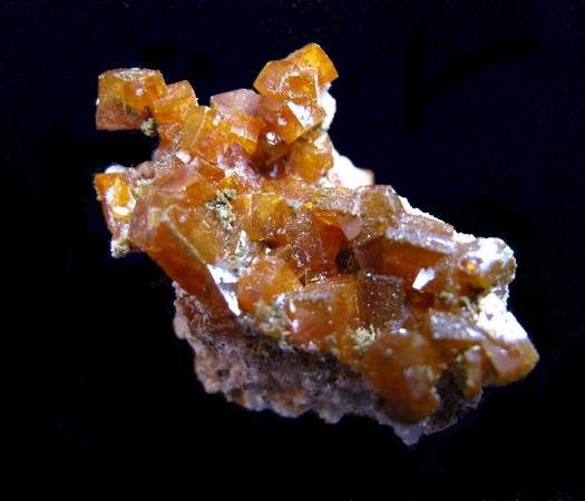 Forms flat, often perfectly square, yellow to orange crystals